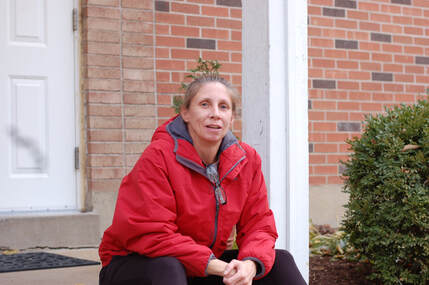 Pictured, a Center for Women in Transition client in front of Baker House.