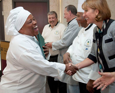 A Center for Women in Transition client wears a chefs hat and shakes the hand of a woman as she graduates her vocational program.